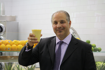 Duane Reade and Walgreens Everyday Living Solutions President Joe Magnacca samples a smoothie from 40 Wall Street's juice bar.