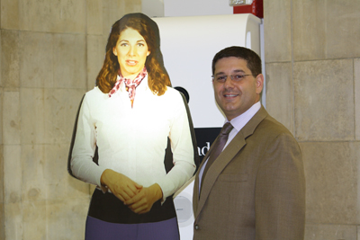 Keith Carpentier (right) stands next to Tensator's Virtual Assistant.