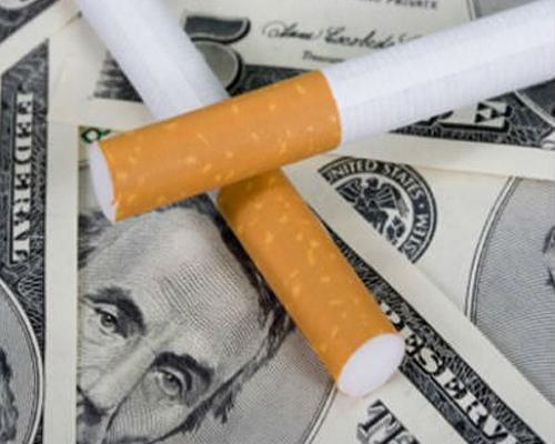 Cigarettes lying on top of dollar bills