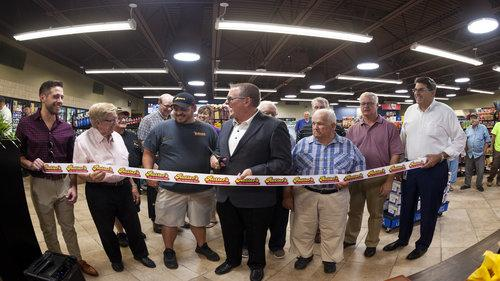 Rutter's President and CEO Scott Hartman prepares to cut the ribbon at grand opening of chain's largest store to date, in front of family members, company associates and customers.