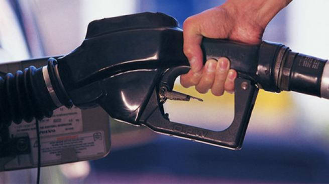 A motorist filling up at a gas station