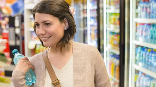 A women buying a beverage in a convenience store