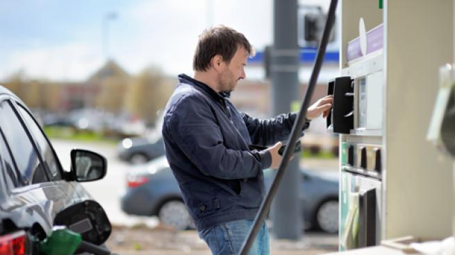 A man paying at the gas pump