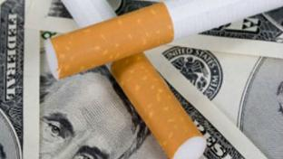 Cigarette laying on top of money