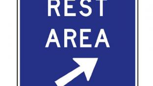 A rest area sign along a highway