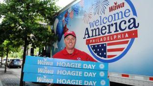 Wawa employee holding hoagies for Wawa Welcome America!