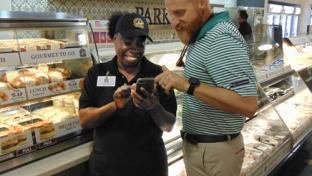 Parker's Chief Human Resources Officer Corey McClimans shows Lucille Washington, deli associate, how to use the new DailyPay technology.